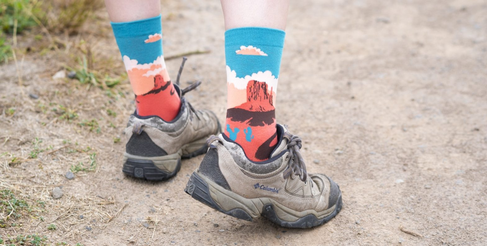 """Feet in hiking boots wearing Sock It to Me """"Monument Valley"""" socks"""
